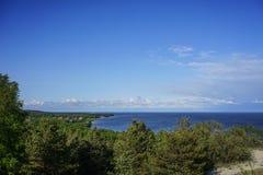 Marinelandschaft mit Ansichten eines kleinen Dorfs umgeben durch Wälder auf dem Curonian-Spucken Lizenzfreie Stockfotos