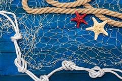 Marinenetz Seil und Starfish auf einer blauen Scheibe Stockfotografie