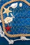 Marinenetz Seil und Starfish auf einer blauen Scheibe Stockfotos