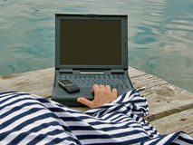 Mariner dress with cellular and laptop. Women with laptop and cellular in harbor Stock Photography