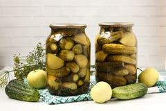 Marinerade gurkor med äpplen i krus är ordnade på en vit bakgrund Royaltyfri Bild