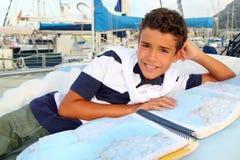 Marinero adolescente del muchacho que miente en correspondencia de la carta del barco del puerto deportivo Imagen de archivo libre de regalías