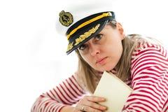 Marinero de la mujer joven en libro de la tenencia del casquillo del capitán foto de archivo