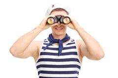Marinero de sexo masculino joven que mira a través de los prismáticos Fotografía de archivo