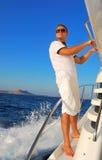 Marinero joven que se relaja feliz en el yach del velero de las vacaciones Foto de archivo