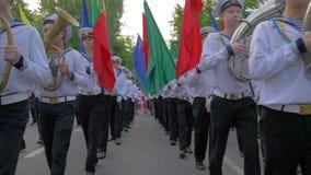 Marineros de Marine Academy en juego uniforme en los instrumentos musicales durante la marcha y llevar banderas coloridas en desf almacen de video