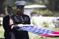 Marinesoldat faltet Flagge an der Gedenkveranstaltung für gefallenen US-Soldaten, PFC Zach Suarez, Ehren-Auftrag auf Landstraße 2 Lizenzfreie Stockfotos
