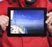 Marinheiro do homem que mostra o barco do iate na tabuleta sailing fotos de stock