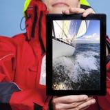 Marinheiro do homem que mostra o barco do iate na tabuleta sailing fotografia de stock royalty free