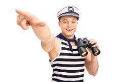 Marinheiro que guarda binóculos e que aponta com sua mão Fotos de Stock Royalty Free