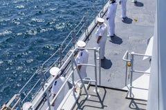 Marinheiros construídos em seguido nos chapéus uniformes e brancos brancos construídos na plataforma de uma tropa do navio da OTA imagem de stock royalty free