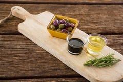 Marinierte Olive, Rosmarin mit Olivenöl und Balsamico-Essig auf Tabelle Stockfotografie
