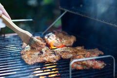 Marinierung des Fleisches während des Grillens Stockfoto