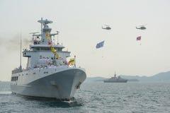 Marinkrigsskepp som kör på havet medan helikopter med att flyga för flaggor Royaltyfria Bilder