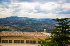 marino SAN Όμορφη άποψη στα βουνά πίσω από τα σπίτια με το ο Στοκ Φωτογραφίες