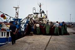 marins pliant leurs filets dans le port de pêche africain à côté d'un marché en gros photos libres de droits