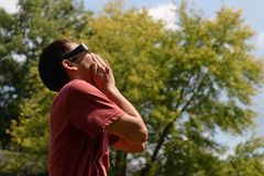Solar Eclipse of August 21, 2017. Marion, IL, USA – August 21, 2017: A man reacts while looking into the sun using solar eclipse glasses in Marion, Illinois royalty free stock images