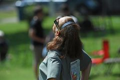 Solar Eclipse of August 21, 2017. Marion, IL, USA – August 21, 2017: A woman looks into the sun using solar eclipse glasses in Marion, Illinois royalty free stock photos