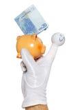 Marioneta del finger que lleva a cabo el piggybank con la nota euro Imagen de archivo libre de regalías