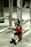 Marionette. Wooden toy as marionette sitting on the ground royalty free stock photography