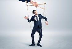Marionettenzakenman leaded door een reusachtige hand stock afbeelding