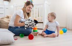 Marionnette de port de sourire de chien de mère en main et jouant avec son b Photo libre de droits