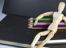 Marionnette en bois se reposant sur le carnet à dessins Image stock