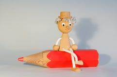 Marionnette en bois se reposant sur un crayon factice de couleur Images stock