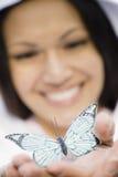 Mariposa sonriente de la explotación agrícola de la mujer foto de archivo libre de regalías
