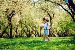 Mariposas de cogida de 3 años del muchacho feliz del niño con la red en el paseo en jardín o parque soleado Activitie al aire lib Imágenes de archivo libres de regalías