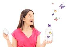 Mariposas de observación de la muchacha feliz que escapan un tarro abierto Fotografía de archivo
