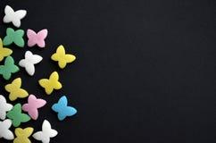 Mariposas multicoloras del azúcar en lado izquierdo el fondo negro, el concepto de primavera y el 8 de marzo, con el copyspace imagen de archivo libre de regalías
