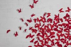 Mariposas rojas en una pared blanca del ladrillo, textura del fondo imágenes de archivo libres de regalías