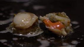Marisco de la cocina de la cámara lenta Almejas del cocinero a del cocinero en los palillos que usan asados a la parrilla metrajes