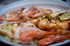 Marisco grelhado delicioso sortido com o vegetal na placa branca Fotografia de Stock Royalty Free