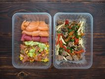 Mariscos con la ensalada y las pastas vegetales con el pavo y el paprika en los envases a llevarse Fotografía de archivo