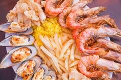 Mariscos con las patatas fritas y el arroz Fotografía de archivo libre de regalías