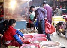Mariscos de la compra de los clientes en el 8vo mercado Foto de archivo libre de regalías