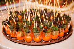 Mariscos de los Canapes en salsa e hierbas en los pinchos de madera Foto de archivo