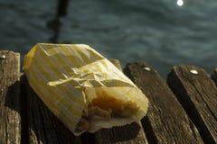 Mariscos fritos en una bolsa de papel en una cubierta cerca del agua imagenes de archivo