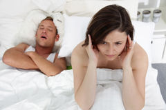Marital problems in the bed. With a women suffering from insomnia trying to block her ears against her husbands loud snores Stock Images