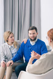 Marital therapy can bring the coveted joy. Happy couple is sitting on the couch during the consultation with psychotherapist Royalty Free Stock Image
