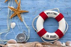 Maritim garnering med skal, sjöstjärna, seglingskepp, fisknät på blått drivaträ royaltyfri fotografi