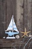 Maritim garnering med skal, sjöstjärna, seglingskepp, fisknät på blått drivaträ royaltyfri foto