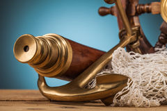 Maritime adventure   telescope anchor and old wooden steering wh Royalty Free Stock Photo