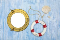 Maritime background with brass porthole and lifebuoy. Maritime background, lifebuoy and sea shells on blue painted wood, brass porthole with copy space Stock Photography