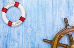 Maritime background with helm and lifebuoy. Maritime background with wooden helm and lifebuoy on blue painted weathered wood Royalty Free Stock Photography
