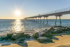 Maritime bridge at sunrise with rocks stock image