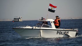 Maritime Coast Guard is moving on a motor boat with the Egyptian flag on the Red Sea. Slow Motion. EGYPT, SOUTH SINAI, SHARM EL SHEIKH, DECEMBER 7, 2016 stock video footage