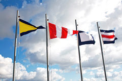Maritime communication streamrs. Maritime communication flags with cloudy sky as background Royalty Free Stock Photo
